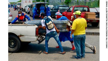 Uomini in equipaggiamento protettivo caricano una bara in un'auto di fronte a un ospedale di Guayaquil.