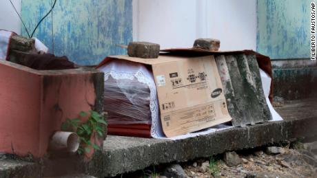 Una bara contenente il corpo di una persona morta di Covid-19 giace avvolta in plastica e coperta di cartone, fuori da un blocco di appartamenti per famiglie a Guayaquil il 2 aprile.