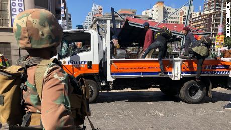 I senzatetto sudafricani a Johannesburg vengono caricati sul retro di un camion della polizia dove viene loro detto che saranno portati in un rifugio per rimanere lì mentre sono in isolamento.