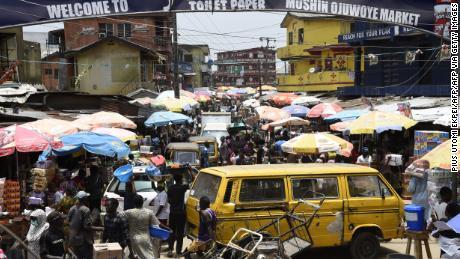 La gente cammina in un mercato affollato in disprezzo di un ordine di spazio sociale, per fare acquisti dell'ultimo minuto prima di un coprifuoco, al mercato Mushin di Lagos.