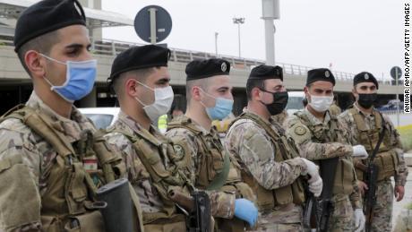 I soldati libanesi, con indosso equipaggiamento protettivo, fanno la guardia all'aeroporto internazionale di Beirut il 5 aprile, prima del ritorno dei cittadini di ritorno.