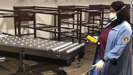 Un medico dell'ufficio del medico legale della Contea di Cook verifica il dispositivo utilizzato per pesare e trasferire i corpi nei rispettivi rack.