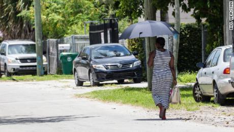 Una donna usa un ombrello per l'ombra quando cammina in una calda giornata a Miami.