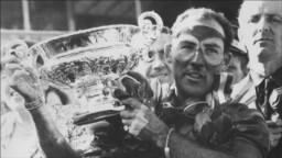 Stirling Moss solleva il trofeo al Gran Premio di Gran Bretagna nel 1955.
