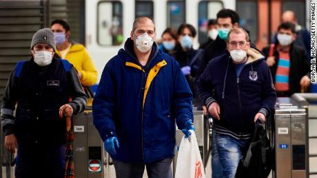 I lavoratori spagnoli indossano maschere che escono dalla metropolitana il 13 aprile a Madrid.