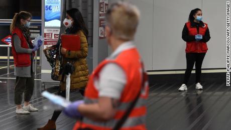 I volontari della Croce Rossa spagnola distribuiscono maschere alla stazione Chamartin di Madrid il 13 aprile.
