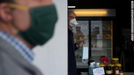 Un lavoratore detiene maschere distribuite da volontari spagnoli della protezione civile.