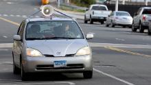 Una persona guida un'auto con un megafono attaccato al tetto per protestare contro l'immigrazione e i costumi di Hartford, Connecticut, 2 aprile.