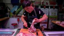 In questa foto scattata il 10 luglio 2019, un macellaio taglia un pezzo di maiale nella sua bancarella in un mercato di Pechino.