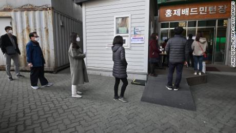 I sudcoreani aspettano in fila per votare alle elezioni parlamentari in un seggio elettorale di Seoul.