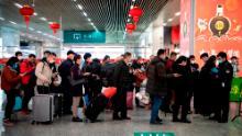 I passeggeri mascherati fanno la fila per mostrare un codice QR verde sui loro telefoni di sicurezza all'arrivo alla stazione di Wenzhou a Wenzhou.