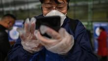 Un passeggero utilizza uno smartphone durante la scansione di un codice QR di salute della città di Wuhan prima di entrare all'aeroporto di Tianhe a Wuhan l'11 aprile.