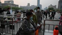 I passeggeri controllano il proprio codice sanitario di Wuhan fuori dalla stazione di Hankou a Wuhan l'8 aprile.