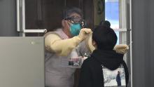 Un membro dello staff medico in una cabina preleva campioni da un visitatore per il test del coronavirus Covid-19 presso una stazione di prova walk-in presso il complesso sportivo Jamsil di Seoul il 3 aprile 2021.