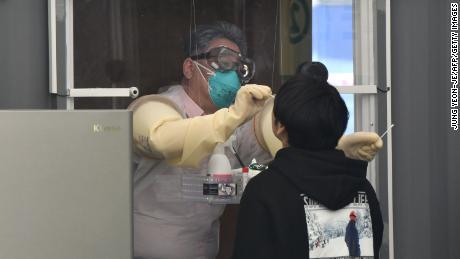 Un membro dello staff medico in uno stand preleva campioni da un visitatore per il test del coronavirus Covid-19 presso una stazione di prova walk-in presso il complesso sportivo Jamsil di Seoul il 3 aprile 2021.