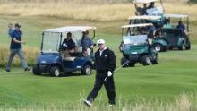 Trump cammina mentre gioca a golf sul campo di Ailsa a Trump Turnberry.