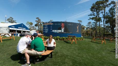 I fan guardano sugli schermi video mentre Monahan parla ai media in una conferenza stampa annunciando che i fan non potranno più partecipare agli eventi del tour PGA.