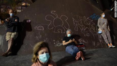 Le persone che indossano maschere protettive partecipano alla manifestazione domenicale.