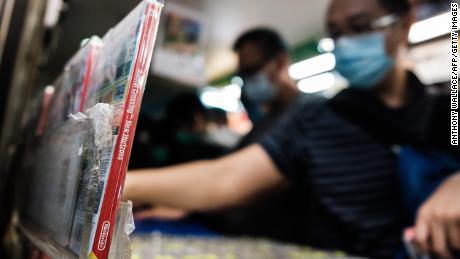 Una copia del gioco per computer Nintendo Animal Crossing: New Horizons (L) viene visualizzata in un centro commerciale mentre i clienti sfogliano altri giochi indossando maschere per il viso, come precauzione contro il coronavirus COVID-19, a Hong Kong, 10 aprile 2021. (Foto di Anthony Wallace / AFP / Getty Images)
