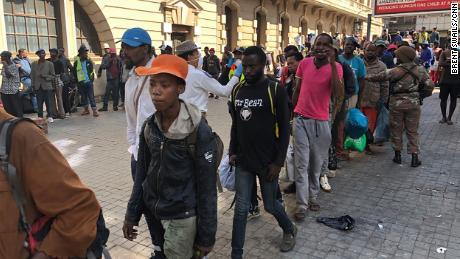 Linee di senzatetto sudafricani attendono il trasporto della polizia verso rifugi temporanei nel centro di Johannesburg.
