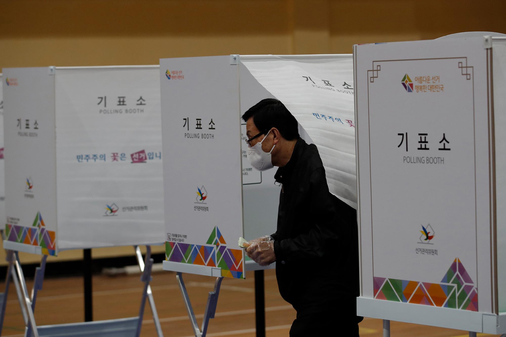 Un elettore che indossa una maschera per proteggersi dalla diffusione del coronavirus esce a votare alle elezioni parlamentari in un seggio elettorale a Seul, in Corea del Sud, mercoledì 15 aprile.