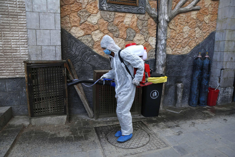 Un membro del team medico spruzza un disinfettante a Sanaa, Yemen, il 6 aprile.