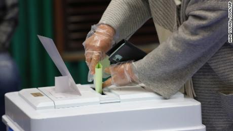 Un elettore che indossa guanti di plastica per proteggersi dalla diffusione del voto sul coronavirus per le elezioni parlamentari in un seggio elettorale di Seoul.