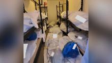 Borse per il corpo e borse blu contenenti gli effetti personali del defunto sono accatastate all'interno di un frigorifero portatile fuori dall'ospedale.