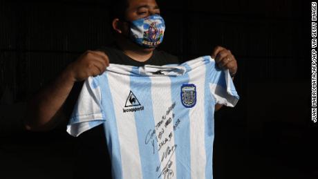 Un uomo detiene una replica della maglia della squadra di calcio argentina utilizzata nella finale della Coppa del Mondo del 1986 e firmata da Diego Maradona.