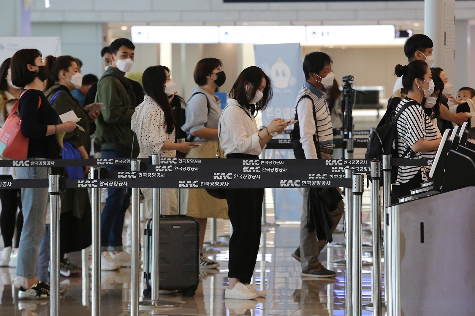 I passeggeri che indossano maschere si allineano per salire a bordo dei loro aerei al terminal di volo nazionale dell'aeroporto Gimpo di Seoul il 27 maggio.