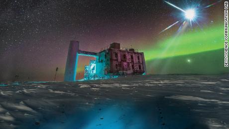In questo rendering artistico, basato su un'immagine reale dell'IceCube Lab al Polo Sud, una fonte distante emette neutrini che vengono rilevati sotto il ghiaccio dai sensori IceCube.