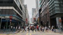 I pedoni che indossano maschere protettive attraversano una strada durante le ore di punta del mattino nel quartiere Kwun Tong di Hong Kong il 6 maggio.