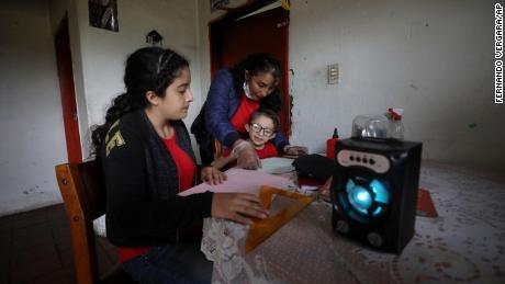 Una famiglia ascolta una lezione radiofonica di un'ora dalla loro casa a Funza, in Colombia, dove non hanno una connessione Internet.